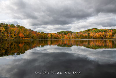 Clouds and autumn reflections on calm pond